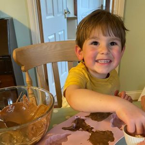 smiling while using kids chocolate making kit